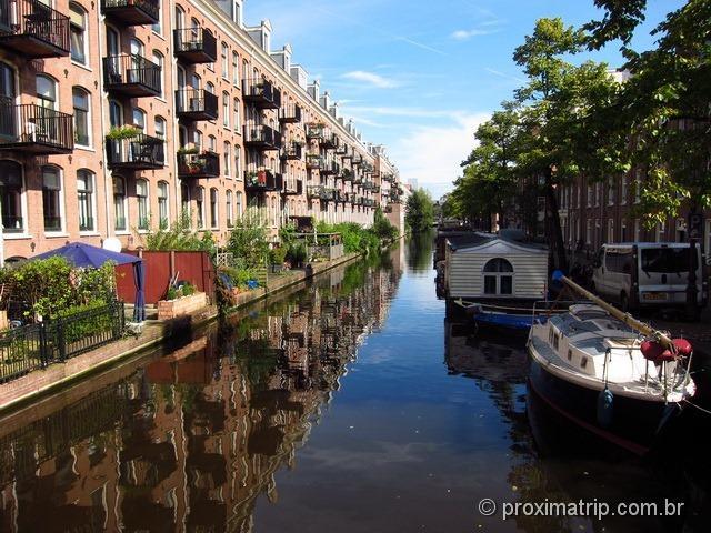 """Lindo canal em Amsterdam refletindo o céu azul, com barcos tipo """"casa"""" flutuante"""