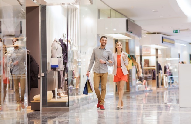 Sale consumerism and people concept happy young couple with shopping bags walking in mall