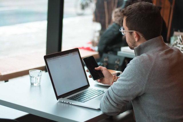 Homem utilizando notebook e smartphone